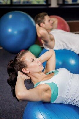 Mann und Frau arbeiten auf Fitness-Ball