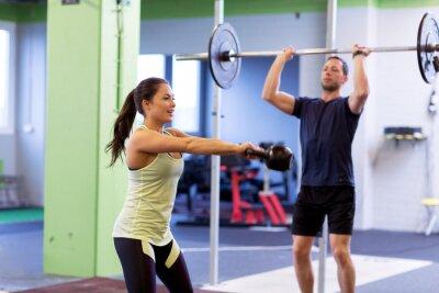 Mann und Frau mit Gewichten im Fitnessstudio trainieren