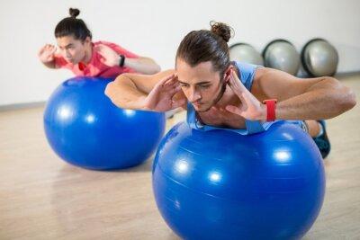 Männer trainieren auf Übungskugel