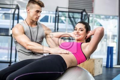 Männliche Trainer assistierende Frau mit sitzen ups