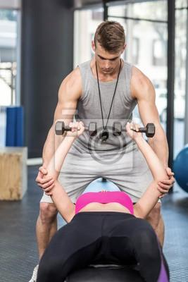 Männliche Trainer helfen Frau Heben Hanteln
