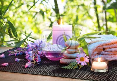 Massage im Bambusgarten mit violetten Blumen, Kerzen