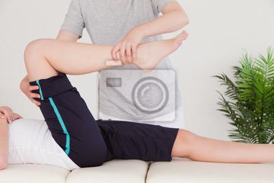 Masseuse Strecken des rechten Beines einer jungen Frau