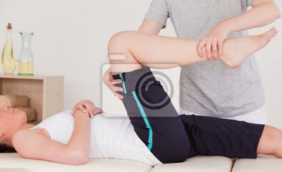 Masseuse Strecken Sie das rechte Bein einer sportlichen Frau