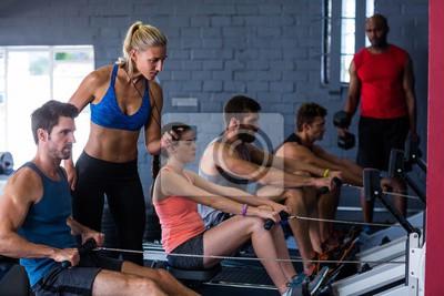 Menschen mit Rudergerät mit Fitness-Trainer in der Turnhalle