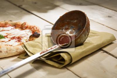 Bild: Mestolo coperto di sugo con pizza margherita affianco sopra carta