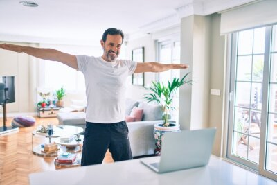 Bild Middle age man with beard training and stretching doing exercise at home looking at sport video on computer