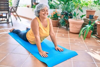 Bild Middle age woman with grey hair smiling happy doing exercise and stretching on the terrace at home