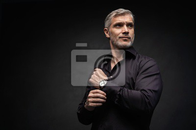 Bild Middle-aged good looking man posing in front of a black background with copy space.