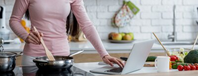 Bild Millennial woman in kitchen cooking with reference the laptop