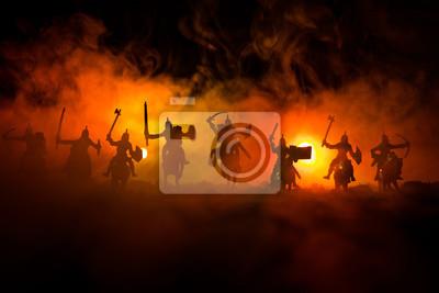 Bild Mittelalterliche Kampfszene mit Kavallerie und Infanterie. Schattenbilder von Zahlen als unterschiedliche Gegenstände, Kampf zwischen Kriegern auf dunklem getontem nebeligem Hintergrund. Nachtszene.