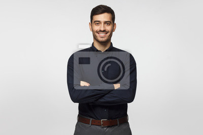 Bild Modern businessman in deep blue shirt standing with crossed arms, isolated on gray background