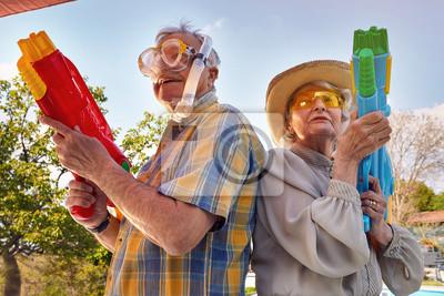 Bild Modern Senior couple have fun playing with  water gun.