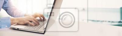 Bild moderner Geschäftsmann, der auf Laptoptastatur im hellen sonnigen Büro schreibt. Exemplar