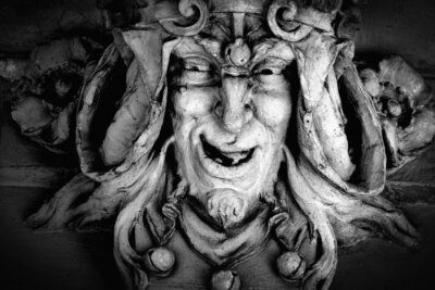 Bild Monster face of aGreek antique god daimon of eager rivalry, envy, jealousy, and zeal Zelus (Zelos). Close up fragment of an ancient stone statue.  Horizontal image.
