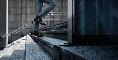 Bild Motivation and challenging Concept. Steps Forward into a Success. Low Section of Businessman Walking Up on Staircase. City Scene