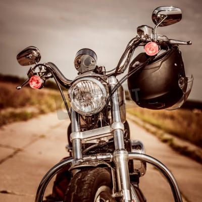 Bild Motorrad auf der Straße mit einem Helm am Lenker.