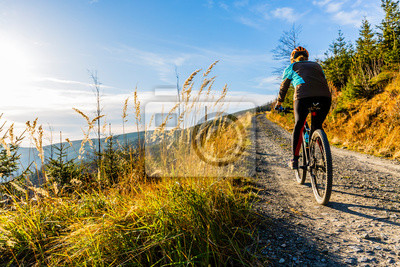 Bild Mountain biking woman riding on bike in summer mountains forest landscape. Woman cycling MTB flow trail track. Outdoor sport activity.