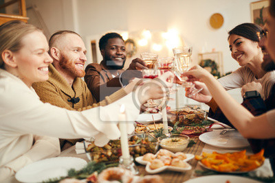 Bild Multi-ethnic group of people raising glasses sitting at beautiful dinner table celebrating Christmas with friends and family, copy space