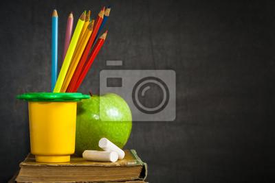 Multicolor Bleistifte, Kreiden und grünem Apfel auf alte Buch
