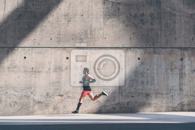 Bild Muscular Male athlete sprinter running fast,exercising outdoors,jogging outside against gray concret background with copy space area for text message or ad content.Side view,full length