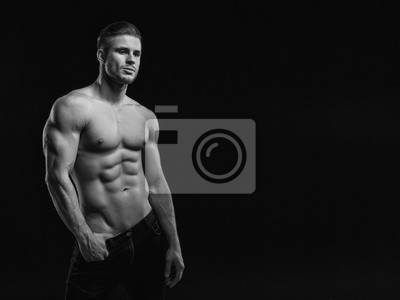Bild Muscular model young man on dark background. Black and white fashion portrait of strong brutal guy with modern trendy hairstyle. Sexy naked torso six pack abs. Male flexing his muscles. Sport concept.