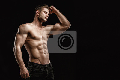 Bild Muscular model young man on dark background. Fashion portrait of strong brutal guy with trendy hairstyle. Sexy naked torso, six pack abs. Male flexing his muscles. Sport workout bodybuilding concept.