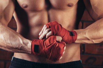 Bild Muskelkämpfer mit roten Verbänden vor dem Hintergrund einer Mauer