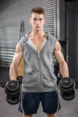 Muskuläre Mann mit grauen Jumper halten Hanteln