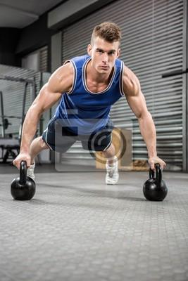 Muskuläre Mann tun Push-up mit Kettlebells