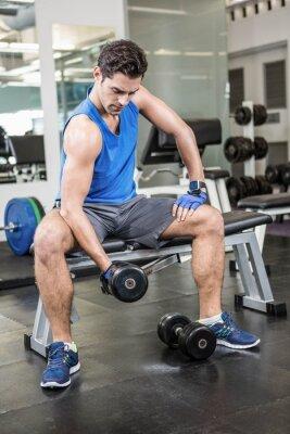Muskulösen Mann Aufhebung Hantel beim Sitzen auf der Bank