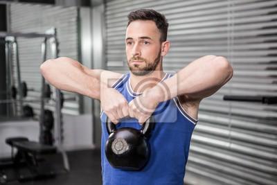 Muskulösen Mann hebt schwere Kettlebell
