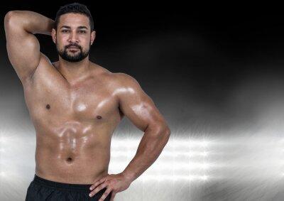 Muskulöser Mann posiert gegen schwarz beleuchteten Hintergrund