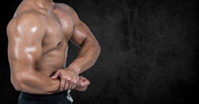 Muskulöser Mann posiert vor schwarzem Hintergrund