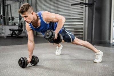 Muskulöser Mann treibt mit Hanteln hoch