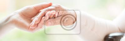 Bild Nahaufnahme der zarten Geste zwischen zwei Generationen. Händchenhalten der jungen Frau mit einer älteren Dame. Der Hintergrund jedoch unscharf. Panorama.