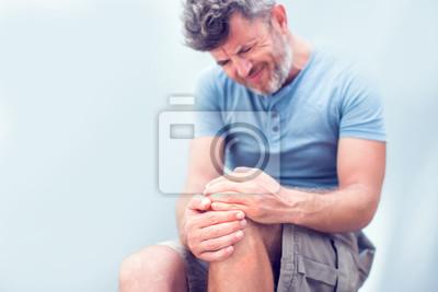 Bild Nahaufnahmemannhand, die Knie mit Schmerz auf Bett, Gesundheitsfürsorge und medizinischem Konzept hält