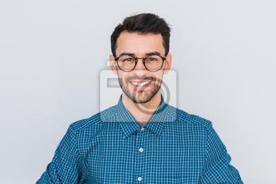 Bild Nahaufnahmeporträt des hübschen intelligent-schauenden Lächelns mit der toothy Lächelnmannesaufstellung für die Sozialanzeige, lokalisiert auf weißem Hintergrund mit Kopienraum für Ihre fördernden Inf