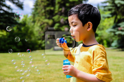 Netter Junge bläst Seifenblasen