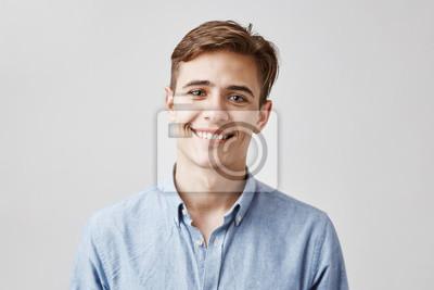Bild Netter Junge mit dem braunen Haar und schönen dem Lächeln, das nahe bei der Wand steht. Sein Geburtstag ist heute so eine Überraschungsparty für Mitarbeiter. Guy sieht glücklich aus, er hat nicht erwa