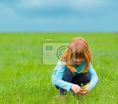 Nettes kleines Mädchen pflücken Blumen auf der Wiese am bewölkten Tag