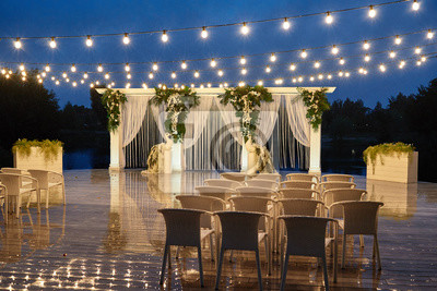 Bild Night wedding ceremony with arch, orchid flowers, chairs and bulb lights in forest outdoors, copy space. Wedding decorations