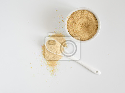 Bild Nutritional yeast. Nutritional inactive yeast in small white ctramic bowl and white ceramic spoon. Copy space. Top view. Nutritional yeast is vegetarian superfood with cheese flavor, for healthy diet