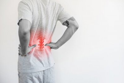 Bild Office syndrome, Backache and Lower Back Pain Concept. a man touching his lower back at pain point