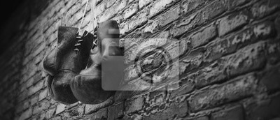 Bild Old boxing gloves hang on nail on brick wall with copy space for text. High resolution 3d render