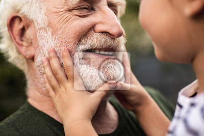 Bild Old smiling man and his granddaughter looking each other
