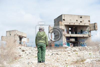 Bild one little lonely child in green jacket standing on ruins of destroyed buildings in war zone