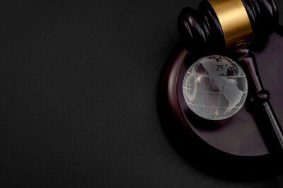 Bild One world government, worldwide global legal system and international law concept with wooden judge gavel and glass atlas or globe isolated on black background with copy space