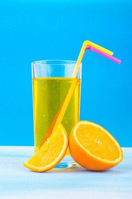 Bild Orangensaft in einem Glas mit farbigen Strohhalmen und Orangenscheiben auf einem blauen Hintergrund