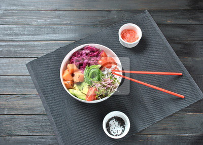 Bild Organic food. Fresh seafood recipe. Fresh salmon poke bowl with rice, fresh red cabbage, avocado, cherry tomatoes, cucumber, radish sprouts on wooden background. Food concept poke bowl